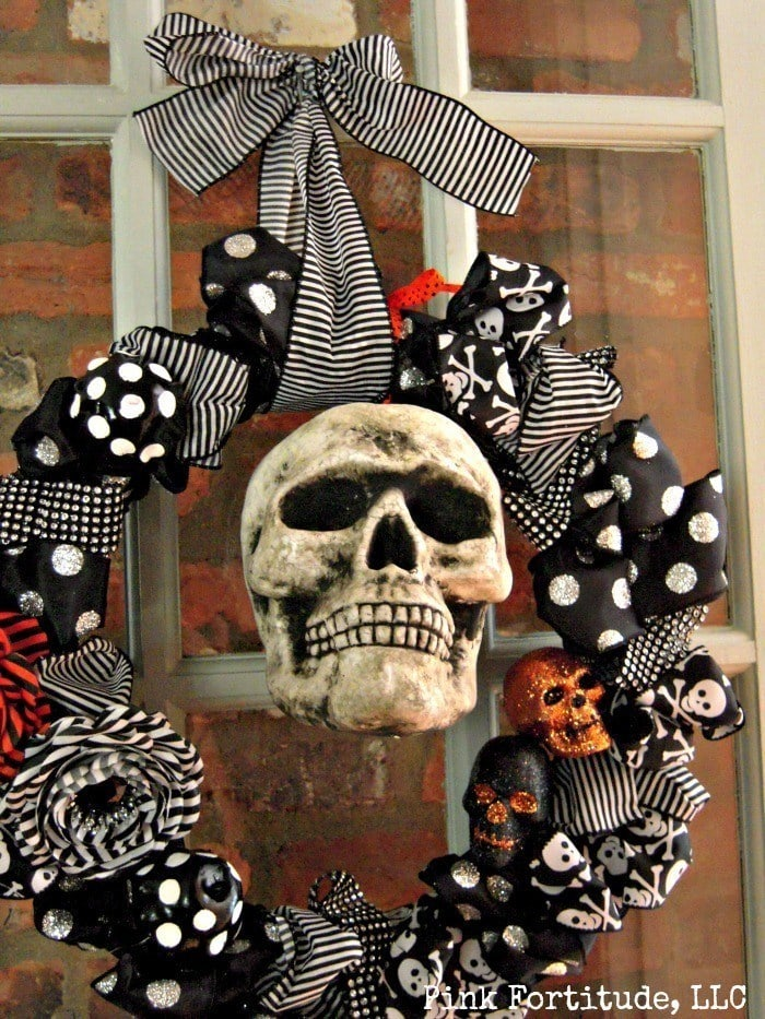 DIY Halloween decor wreath with black and white fabric bows, ribbons and glitter skulls.