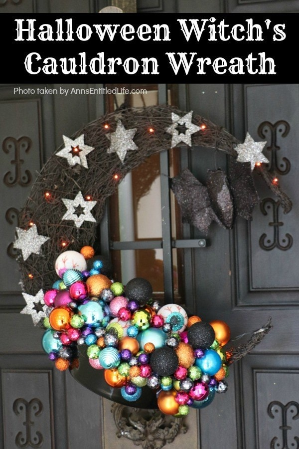 Crescent shaped wooden wreath with colorful ornaments, silver glitter stars and twinkle lights.