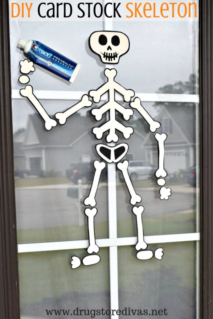 Skeleton made from prints card stock hung in a window holding a tube of toothpaste.