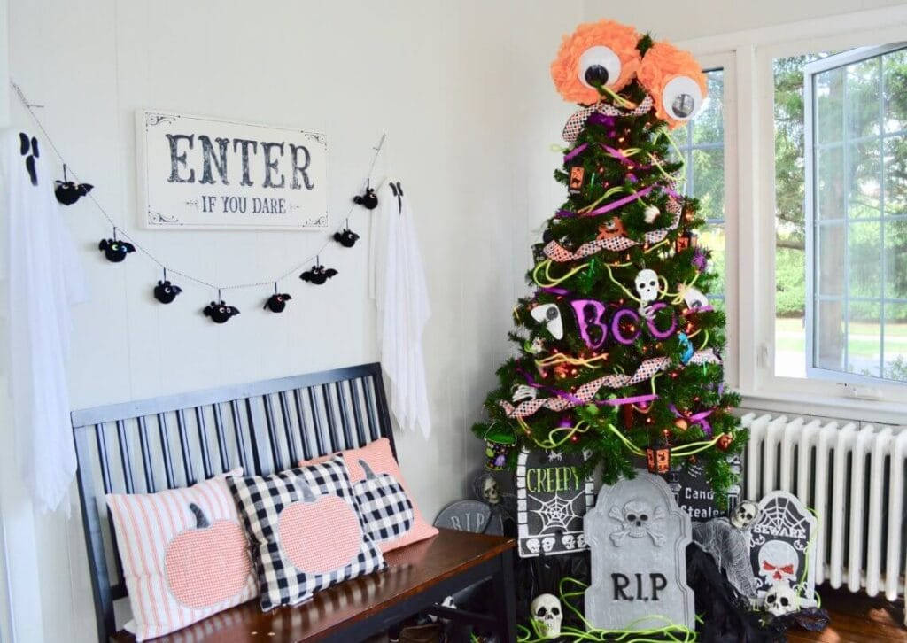 Christmas tree decorated with DIY Halloween decorations in a bright room next to a bench with Halloween pumpkin throw pillows.
