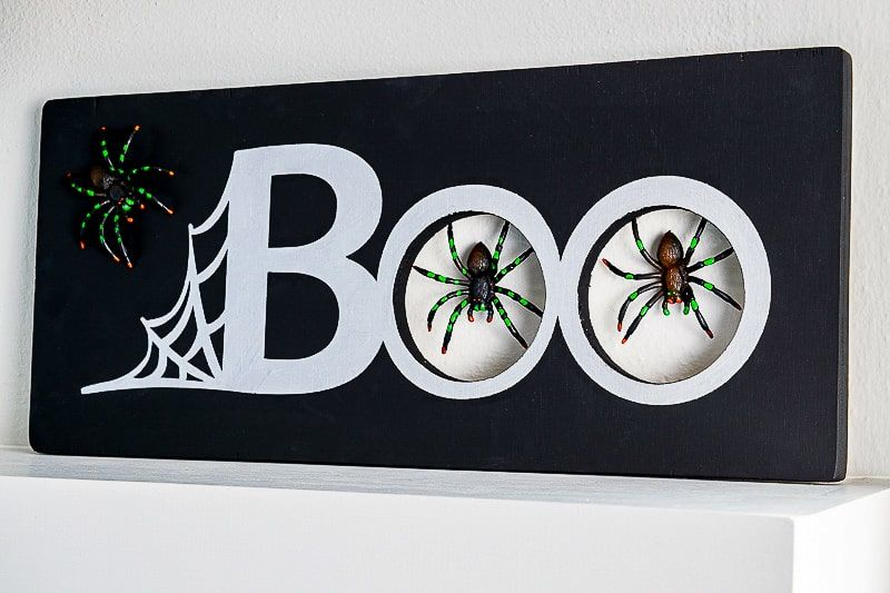 Wooden boo sign with plastic spiders: DIY Halloween decoration ideas.