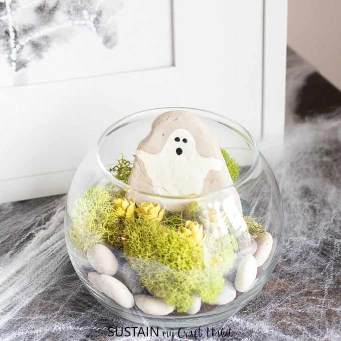 Glass Halloween terrarium with stones, moss and a ghost painted on a rock is a cute DIY Halloween decor idea.