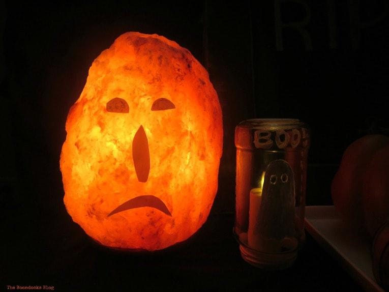 Himalayan salt lamp made into a Jack o' Lantern is a cheap DIY Halloween decor idea.