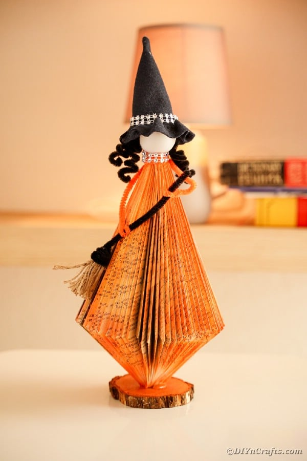 Cute orange witch holding a broom made from an old book.