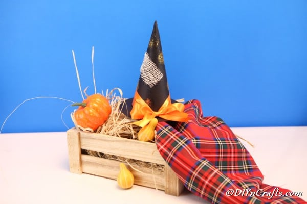DIY Halloween decor witch hat in a wooden crate styled with hay, small faux pumpkin and squash and red plaid fabric.