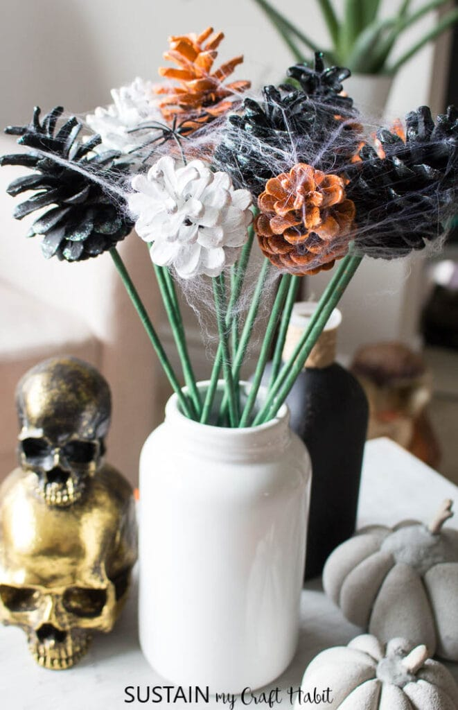 Painted pine cone bouquet in a white jar and styled with gold skulls make great DIY decor for Halloween.