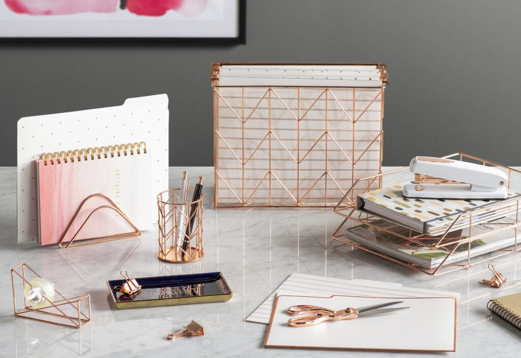 Rose gold metal file box, paper holders, pencil cup, tape dispenser, scissors, stapler, clips, decorative tray and file folders atop a white marbled desk.