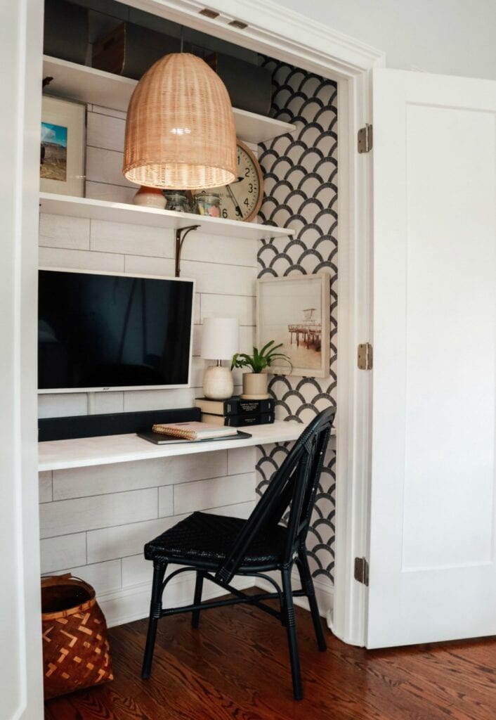 An office set up inside of a closet with shelving covered in decorative plants, books, and framed art surrounding a large computer monitor. Features a fun printed wallpaper and a wicker style pendant lamp overhead.