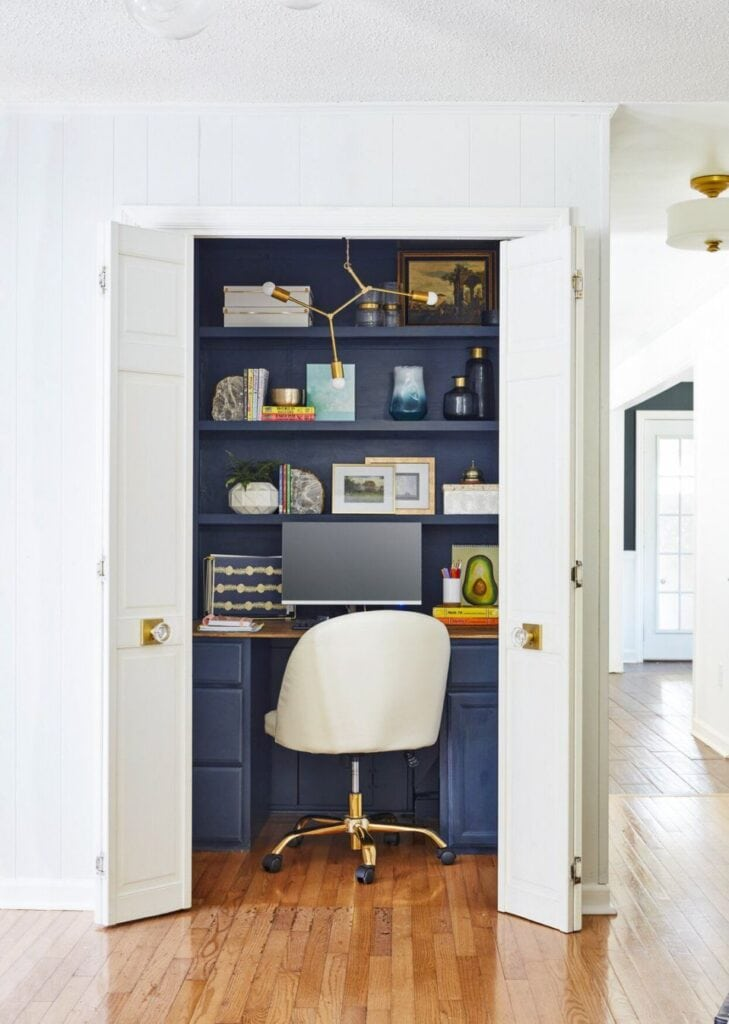 A dark blue painted desk and shelving built inside of a closet. Features a computer and desk top organizers, decorative vases and art prints.