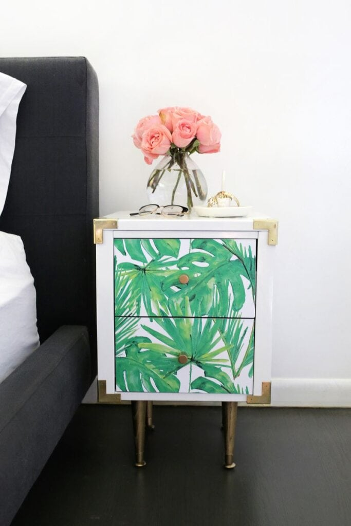 White bedside table with two drawers with temporary paper with green leaves