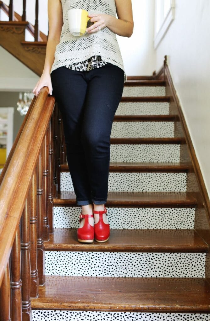 Women walking down temporary usable papered stairs holding yellow and white coffee cup and wearing red shoes.