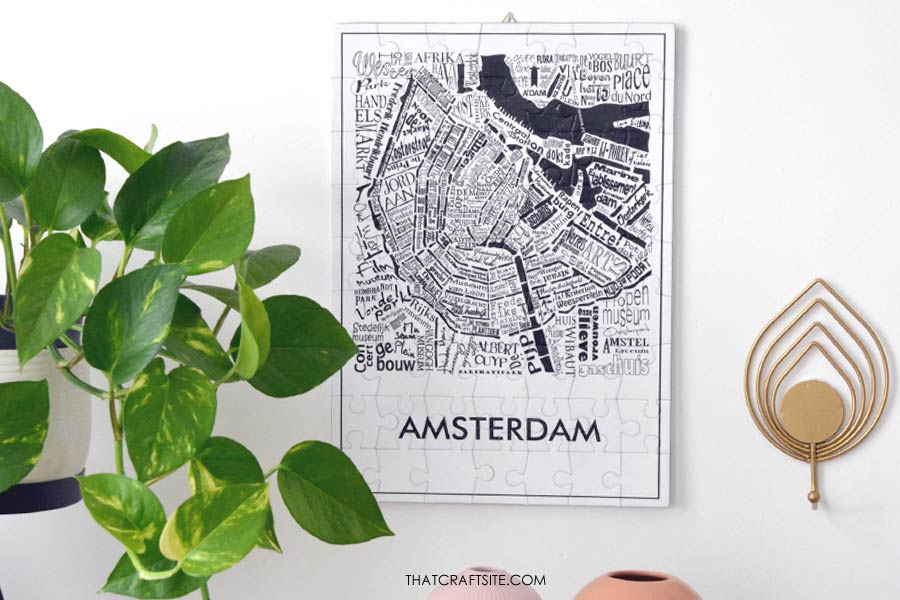 Black and white puzzle of Amsterdam hanging on a white wall next to a green plant.
