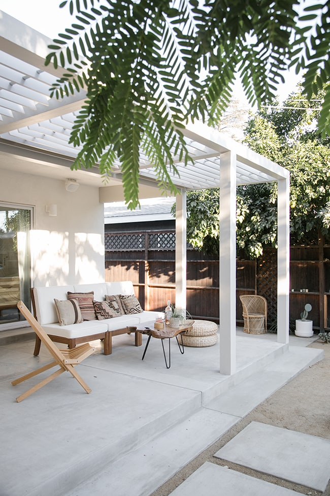 Concrete patio flooring with boho patio furniture and a patio covering.