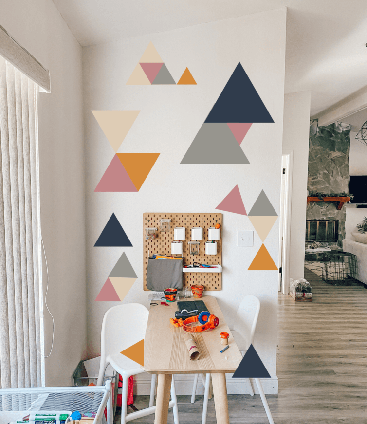 White wall with Blue, Orange, Grey, Pink painted triangles. Table and chairs.