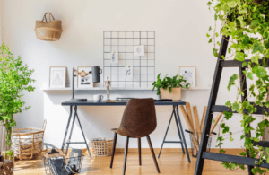 Light bright and airy office with a black desk and a brown chair with lots of plants in the room. Baskets for storage.