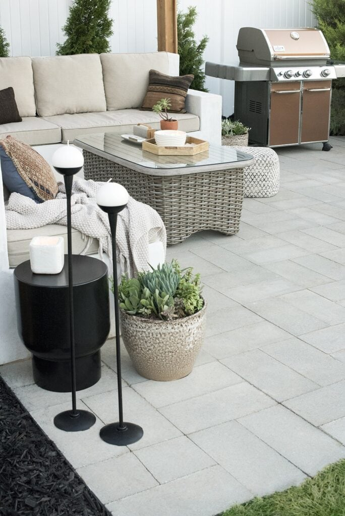 Light grey paver patio flooring with patio furniture and table and grill.