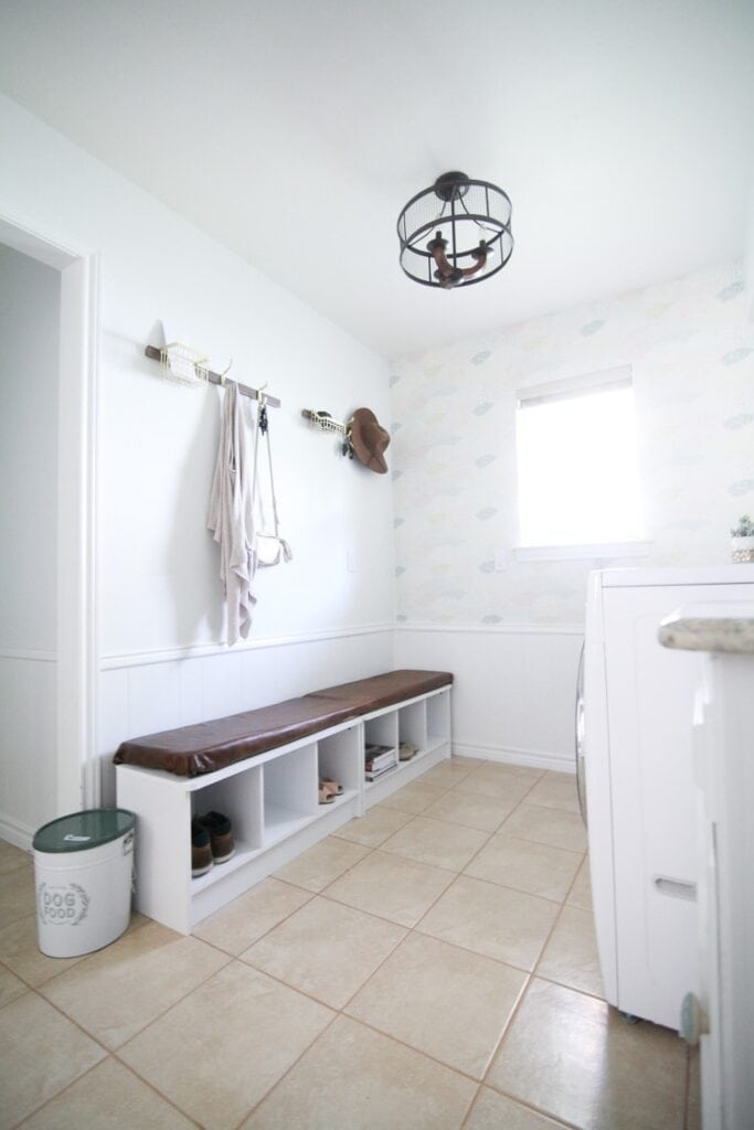 All white laundry room showing half of the wall with temporary paper.
