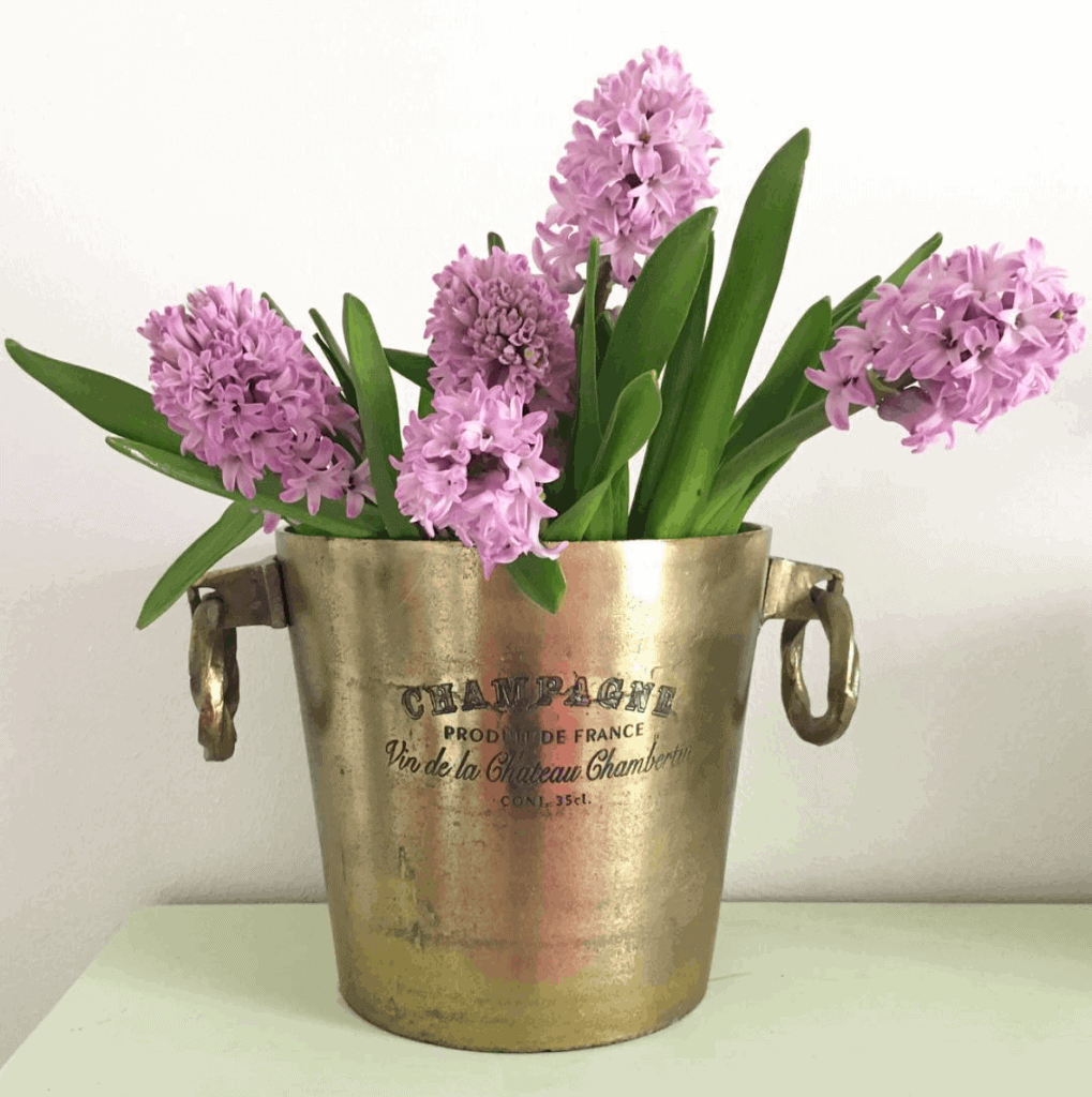 A gold champagne bucket filled with fresh purple flowers stems.