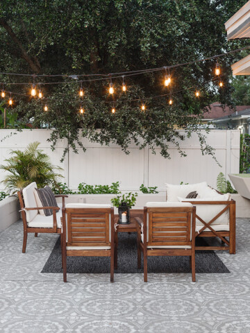 Outdoor patio furniture set outside under trees with lights in the trees. The flooring is an outdoor carpet.