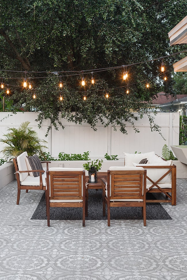 Large outdoor carpet patio flooring with patio furniture set under trees and string lights.
