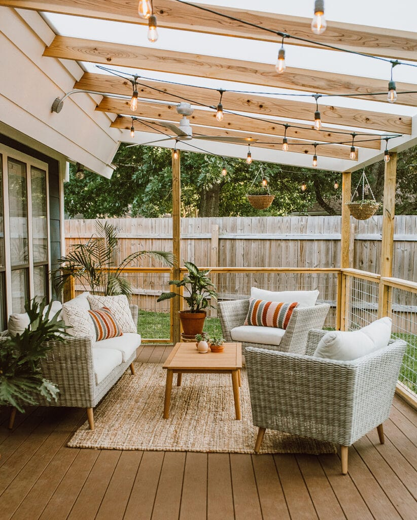 Wood patio flooring with wood patio cover with sting lights and furniture set.