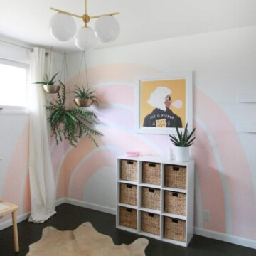 Pink rainbow painted on a white wall in a bedroom.