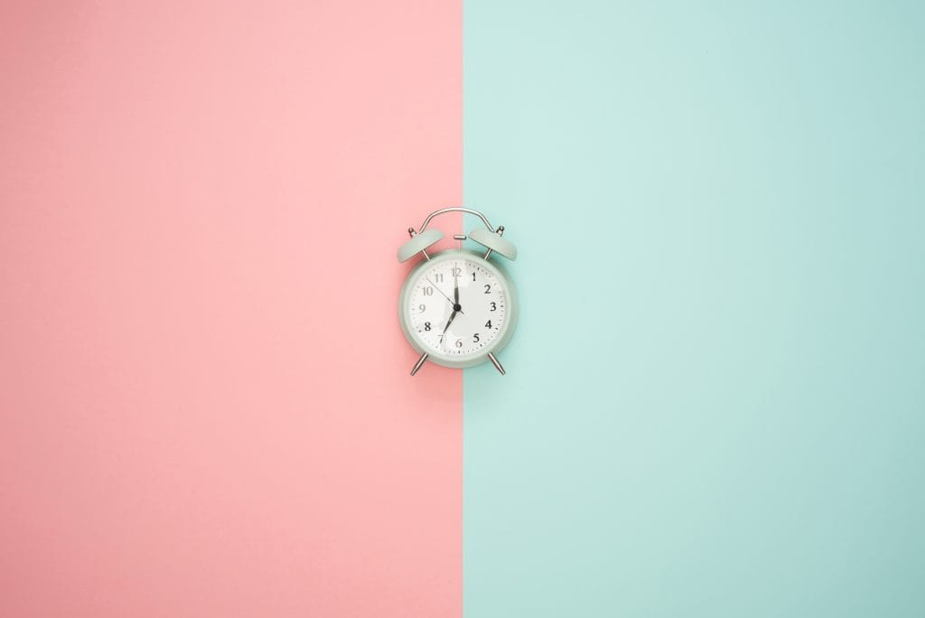 Pink and blue wall with old time alarm clock.