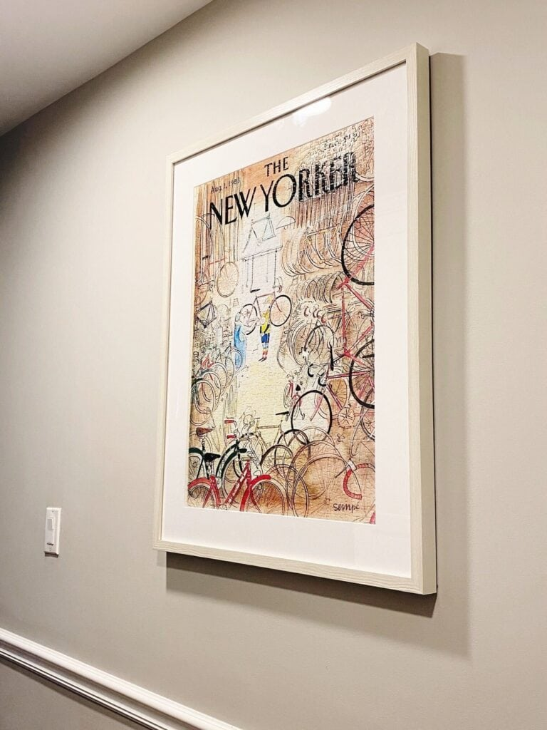 The New Yorker Puzzle framed in a natural wood frame. Hanging on a tan wall.