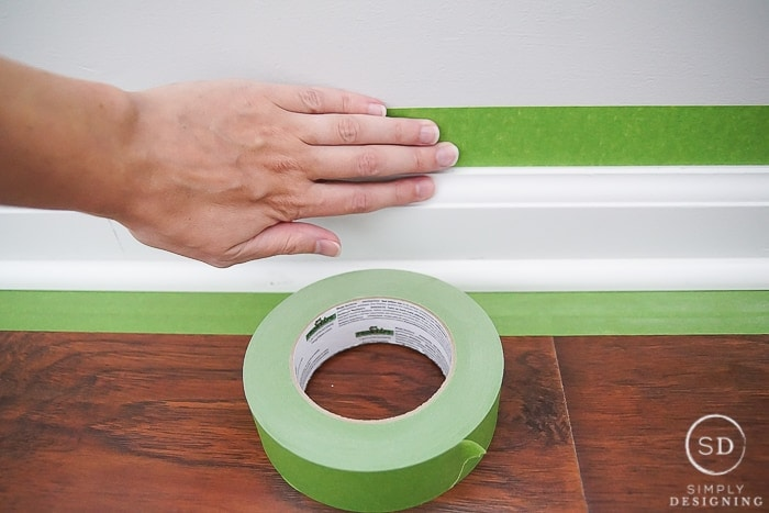 Baseboards with green painters tape.