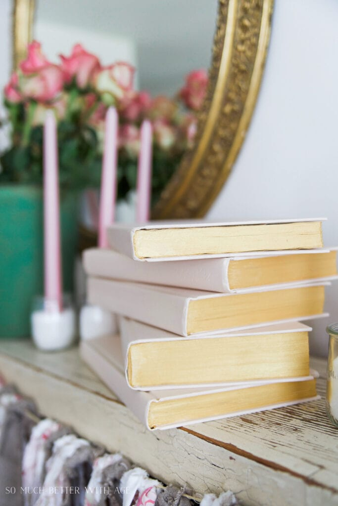 Five pale pink bound books on shelf with candles and flowers.