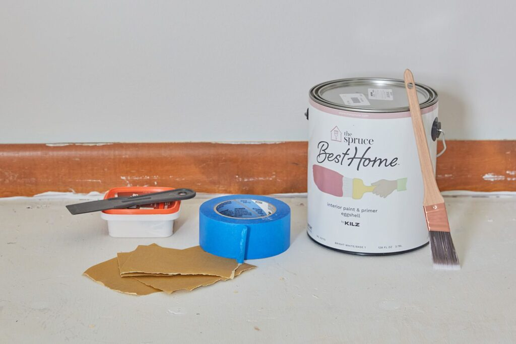 Can of paint with paint brush leaning against it. Blue tape, sandpaper and spackle.