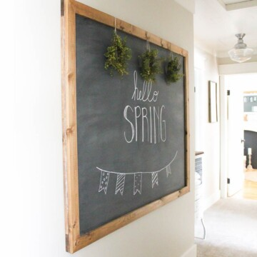 Chalkboard that reads Hello Spring hanging on a white wall.
