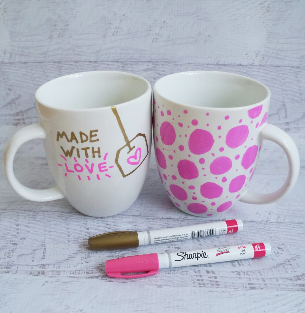 Two white mugs decorated with pink and brown sharpies.