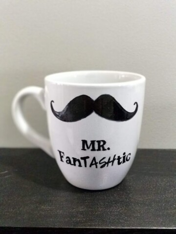 White coffee mug with a mustache drawn on it that reads mr. fantashtic.