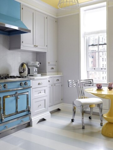 Grey kitchen cabinets with blue stove and yellow kitchen table.