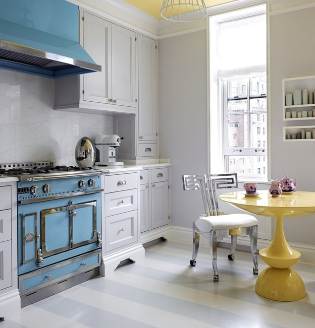Grey kitchen with a blue stove and a yellow table.