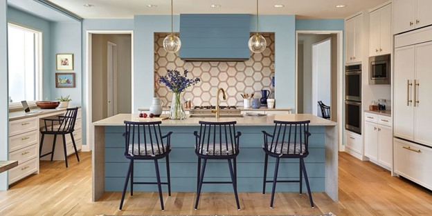 Blue kitchen walls and light grey kitchen cabinets with a light wood floor.
