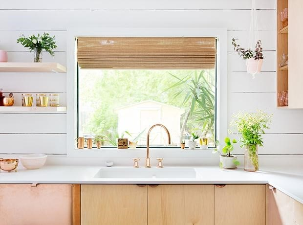 Mostly white kitchen with some pink colored accents.