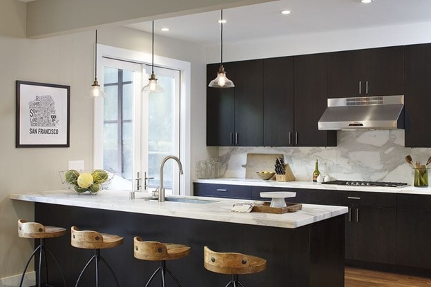 Black kitchen cabinets with tan walls.