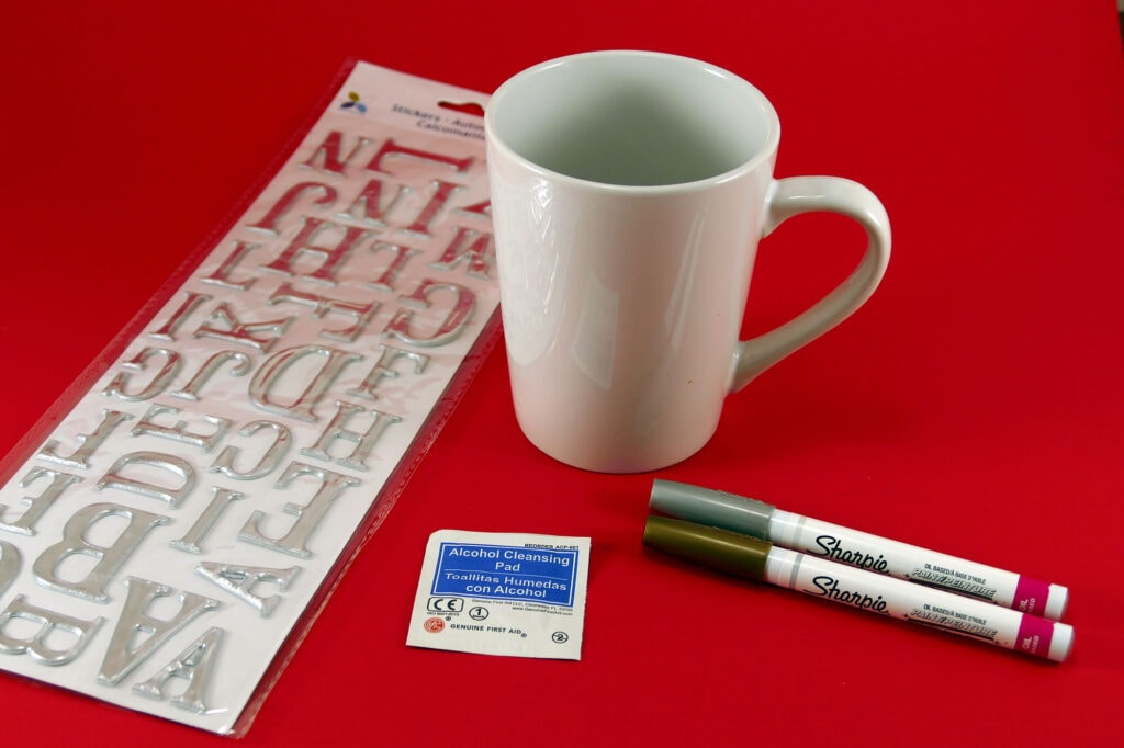 White mug with stickers and 2 sharpies on a red table.