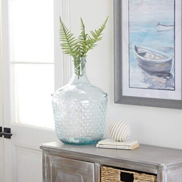 Blue glass bottle on wood side table with white candle and painting of a boat above.