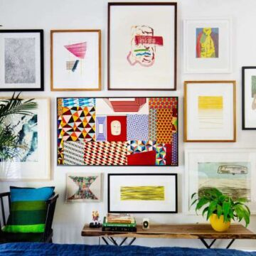 White wall with colorful artwork surrounding a tv.