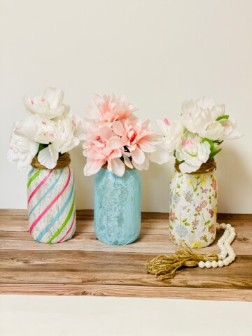 Three mason jar flower vases on a wood countertop.