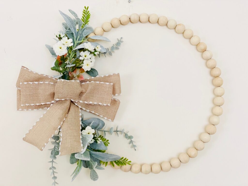 Wood bead wreath with flowers on the left hand side and a tan bow with white piping.