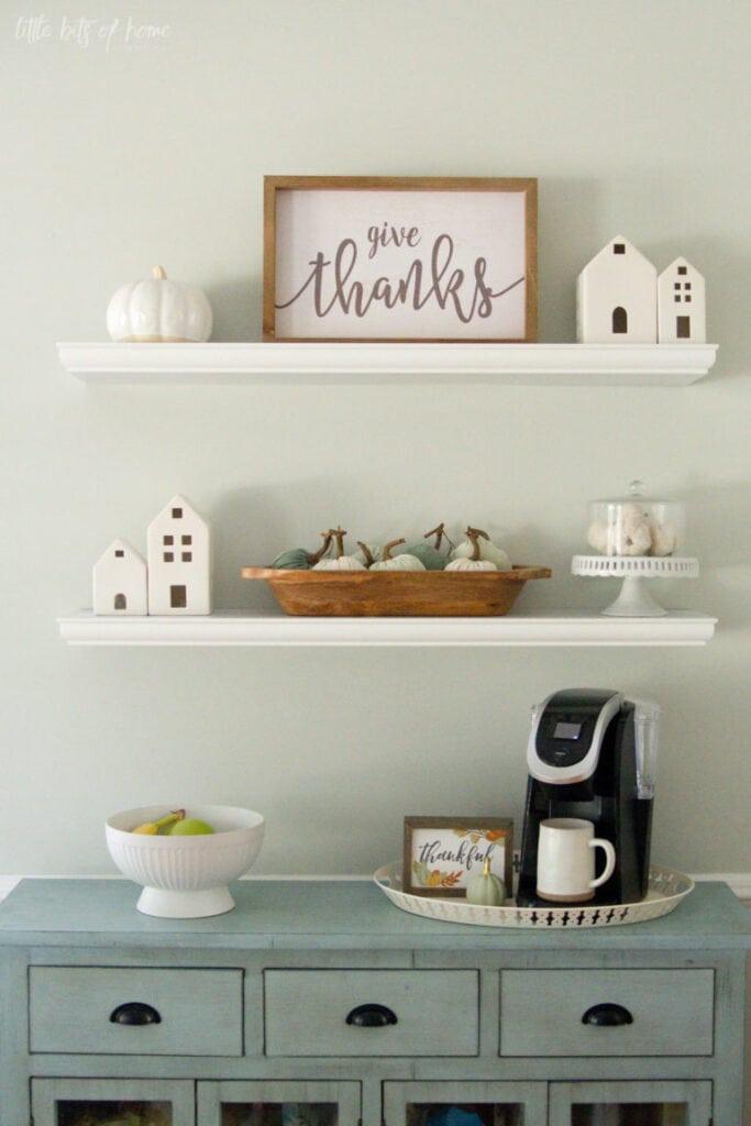 White floating shelves with fall themed seasonal decor items like framed art, ceramic houses and white pumpkins.