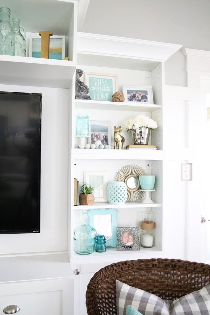 Beach themed shelf decor with blue as an overall color scheme.