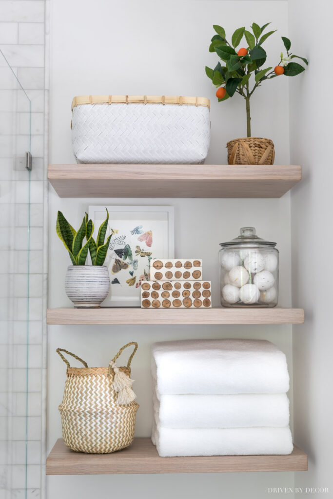 A bathroom shelving unit with white towels, a white basket, and natural decor elements.