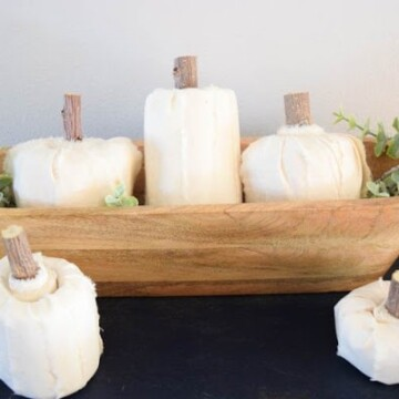 White fabric pumpkins made with sawed off rolls of toilet paper styled elegantly in a wooden bowl and greenery make great DIY Halloween decorations.