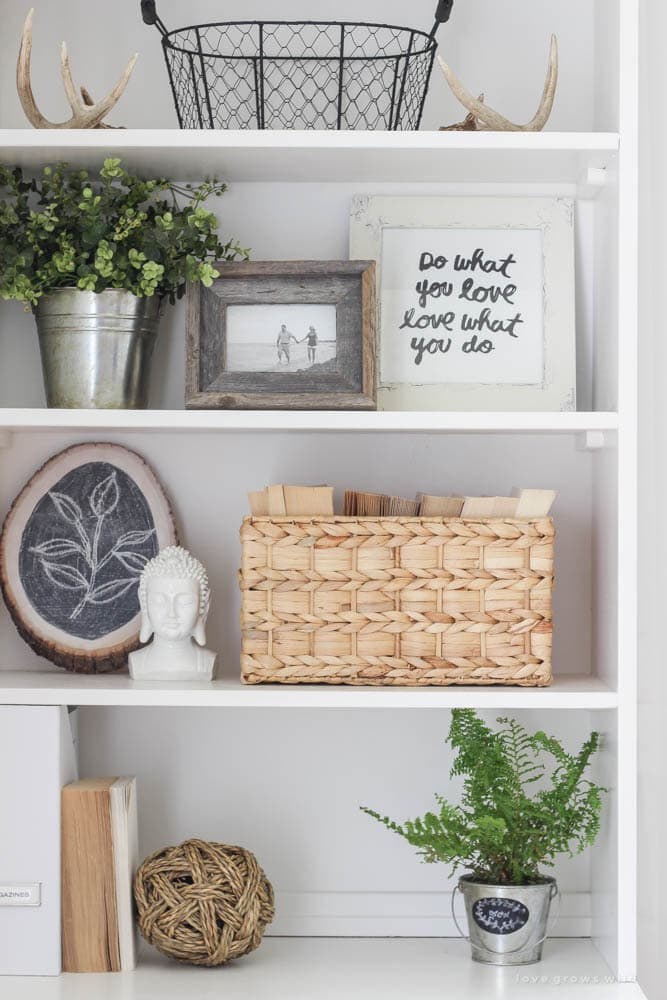 White shelving decorated with differing heights of decor, all in natural tones, with a few faux plants mixed in.