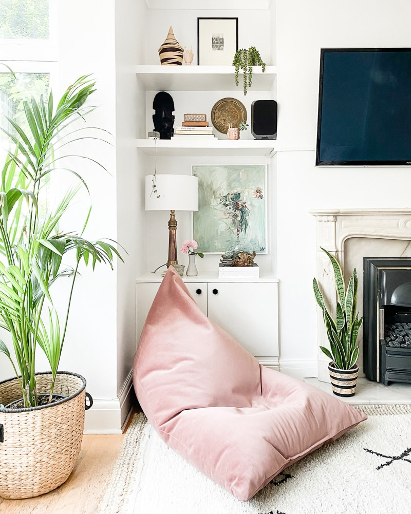 A brightly lit living area with upper and lower shelves, displaying unit decor items and small plants.